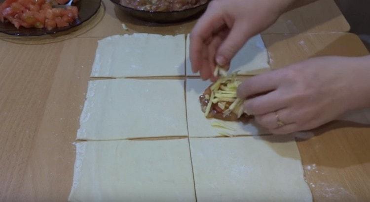 Выкладываем на центр квадрата начинку из мяса, сверху добавляем помидор и сыр.