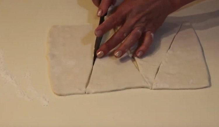 Нарезаем раскатанное тесто на треугольнички.
