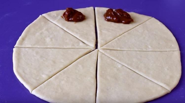У основания каждого треугольника выкладываем ложку вареной сгущенки.