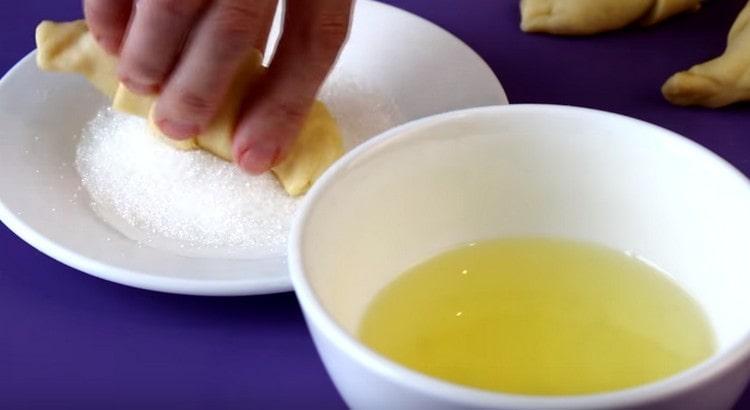 Каждый круассан обмакиваем в белок, оставшийся от яиц, а затем и в сахар.