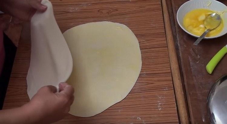 Смазываем каждый круг теста растопленным сливочным маслом и складываем их друг на друга.