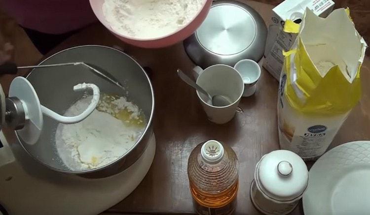 Добавляем часть муки и включаем комбайн, чтобы тесто перемешивалось.