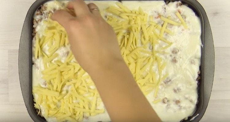 По фаршу распределяем оставшийся соус,посыпаем блюдо сыром и отправляем в духовку.