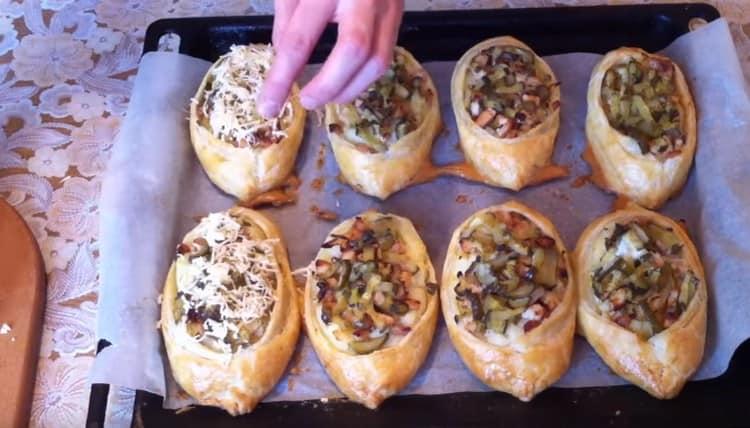 за несколько минут до готовности посыпаем пирожки тертым сыром.