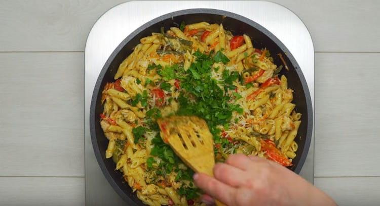 Выкладываем в сковороду макароны, добавляем помидоры и измельченную зелень.
