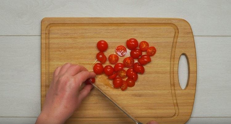 Разрезаем пополам помидоры черри.