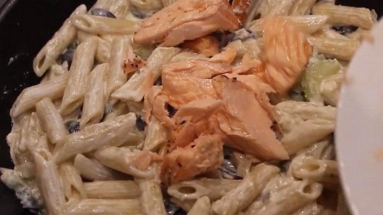 Добавляем к макаронам с соусом кусочки рыбы.