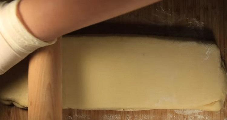 Достав тесто из холодильника, раскатываем его в длину.