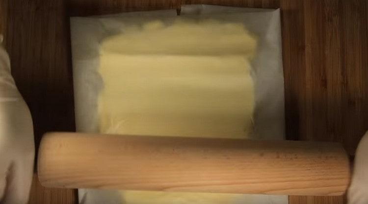 Отдельно между двумя истами пергамента раскатываем до размеров квадрата 20х20 см сливочное масло.