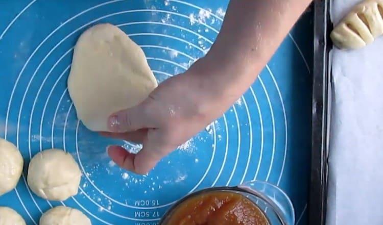 Шарики теста раскатываем скалкой в продолговатые лепешки.