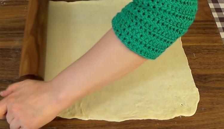 Выкладываем на стол тесто и раскатываем тонко.