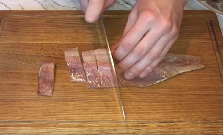 Филе селедки режем на кусочки.
