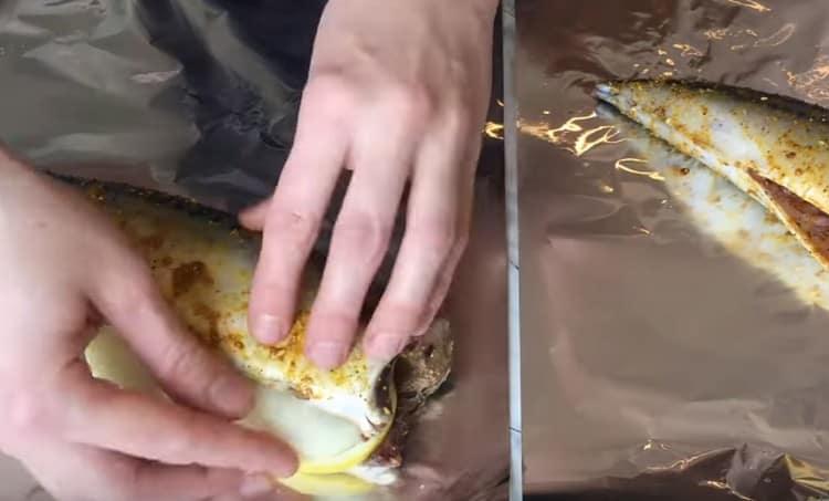 В брюшко рыбы закладываем по несколько кружочков лука и лимона.