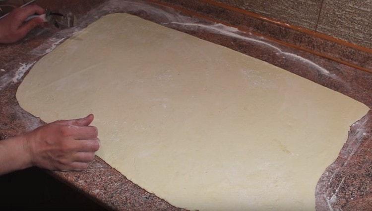 Слоеное тесто тонко раскатываем в большой прямоугольник.