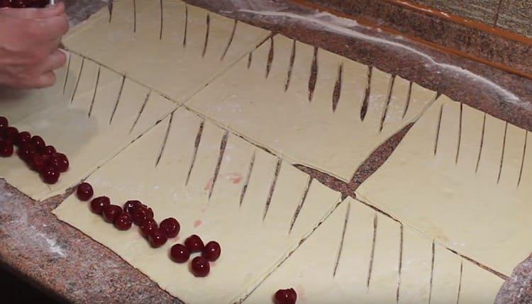 На часть теста без надрезов выкладываем вишни.