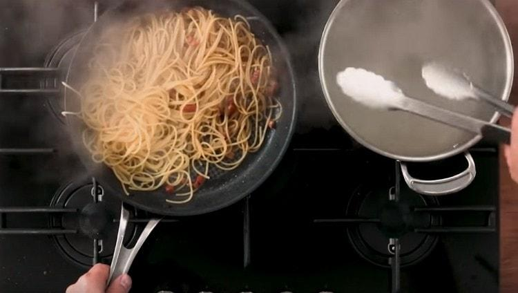 На сковороду добавляем спагетти, предварительно убрав с нее чеснок.