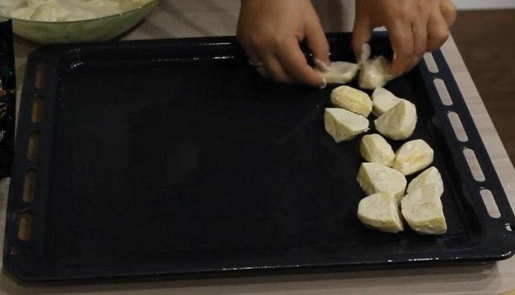 Выкладываем картофель на смазанный растительным маслом противень.