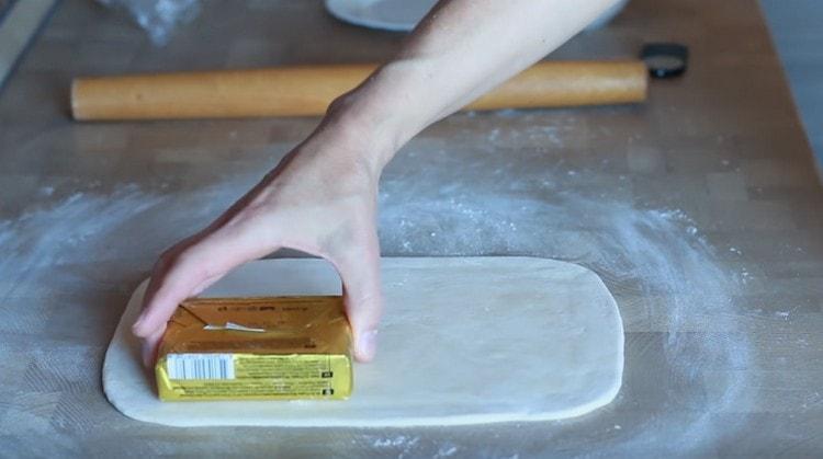 на пласте теста должны вдоль и поперед помещаться две пачки масла.