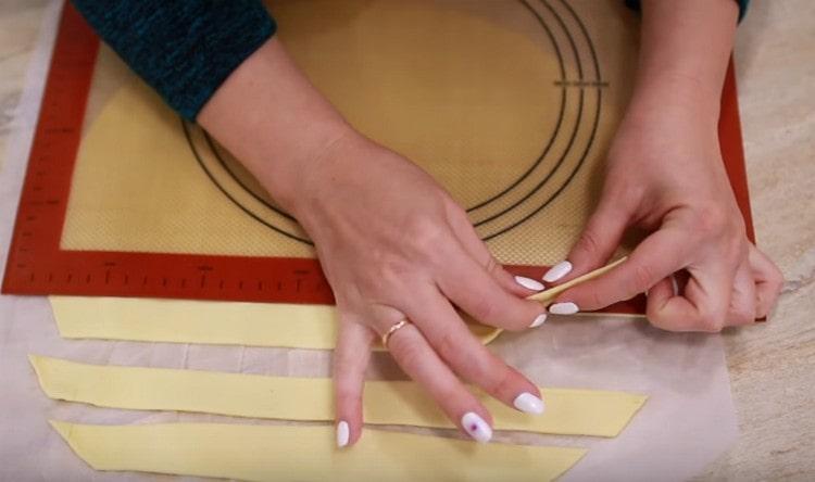 Слоеное тесто тонко раскатываем и нарезаем на тонкие длинные полосы.