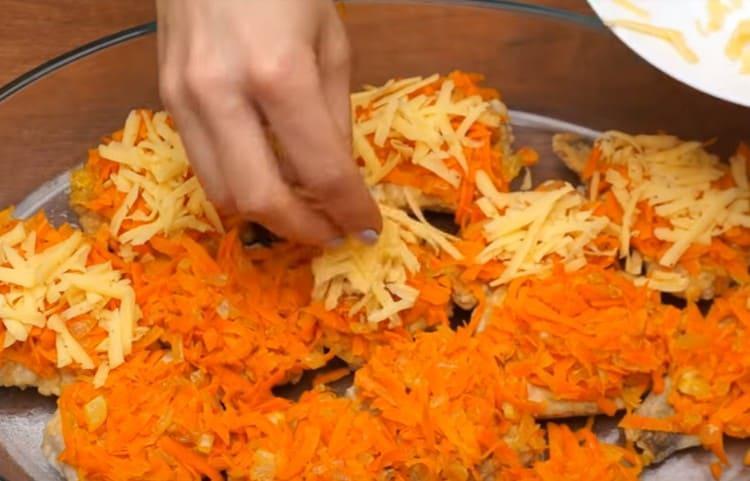 Каждый кусочек рыбы с овощами посыпаем натертым на терке сыром.