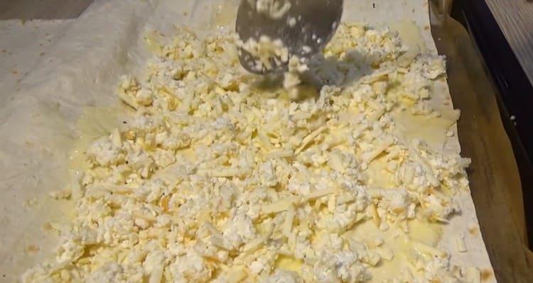 Сверху выкладываем половину сырно-творожной начинки.