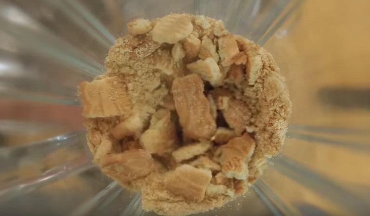 Измельчаем в крошку песочное печенье.