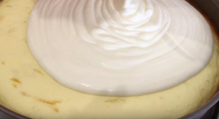Покрываем сметанным кремом почти готовый чизкейк.