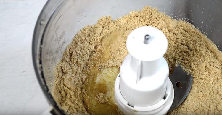 К измельченному печенью добавляем растопленное сливочное масло и перемешиваем.