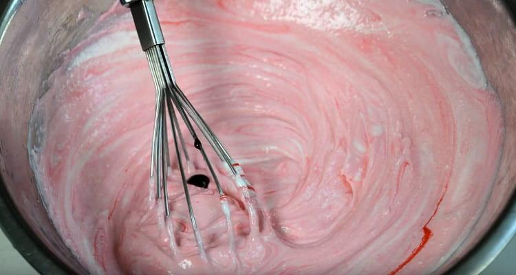 В одну часть творожной массы добавляем красный пищевой краситель и перемешиваем.