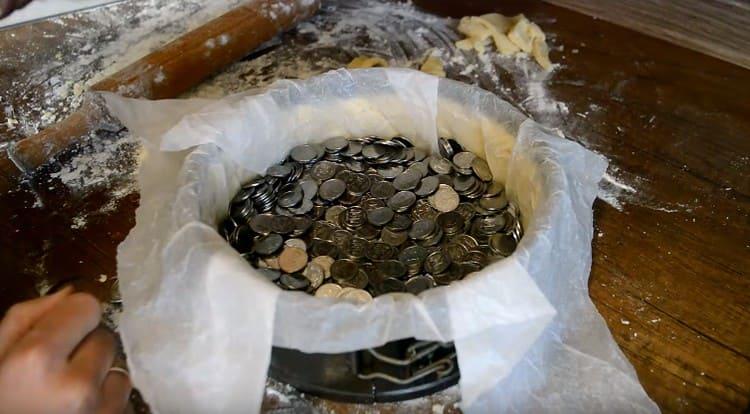 застилаем основу десерта пергаментов и выкладываем туда груз: горох, монетки и т.п.