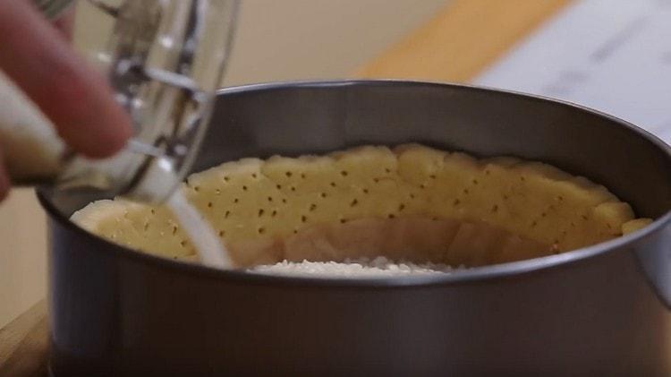 Застелив дно основы пергаментом, насыпаем груз, например, рис.