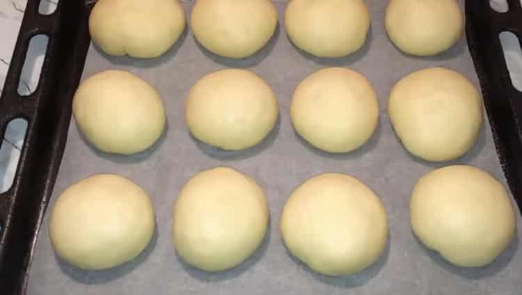 Для приготовления булочек с вареной сгущенкой выложите заготовки на противень