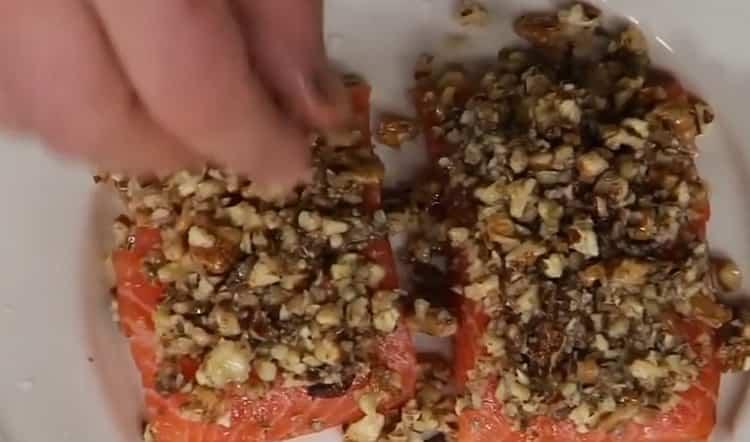 Для пригготовления красной рыбы в духовке, выложите орехи на рыбу