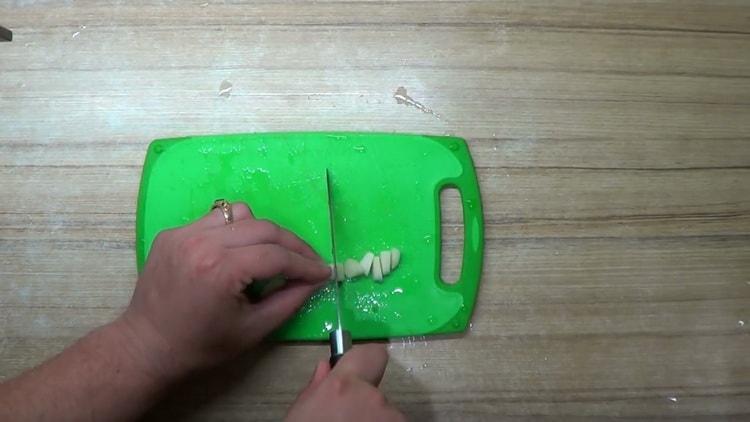 для приготовления окуня в духовке в фольге, нарежьте чеснок