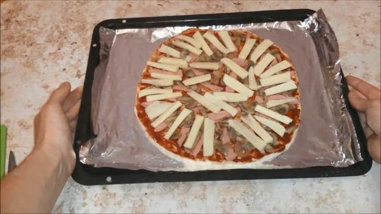 Для приготовления пиццы с колбасой и сыром, разогрейте духовку