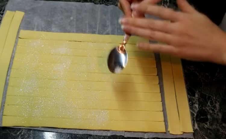 Для приготовления розочек из слоеного теста посыпьте сахаром тесто