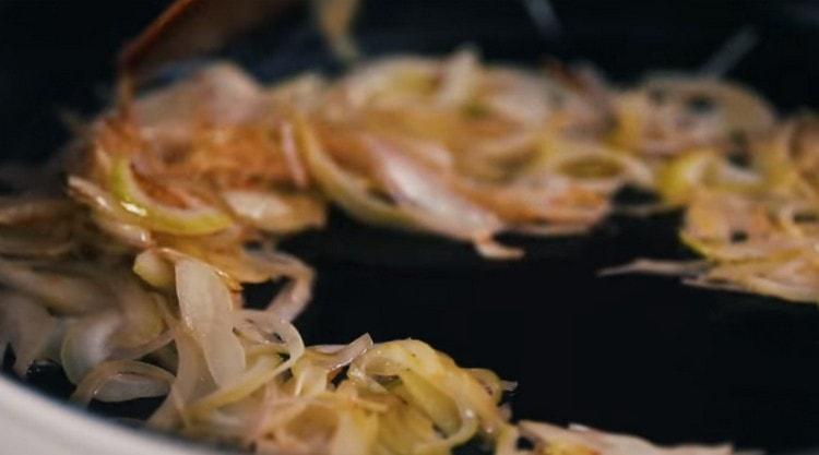 Отдельно на сковороде обжариваем до золотистого цвета нарезанный полукольцами лук.