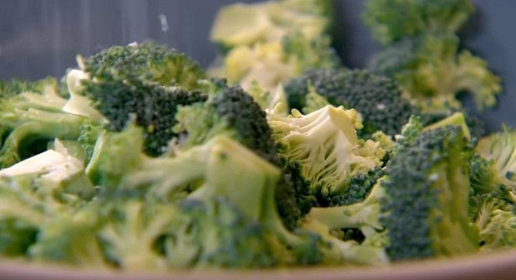 Выкладываем кусочки брокколи в миску и посыпаем крупной морской солью.