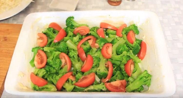 Поверх брокколи раскладываем помидоры.