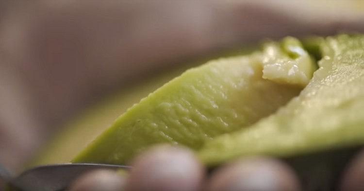 Из разрезанного пополам авокадо удаляем косточку, ложкой выбираем мякоть.