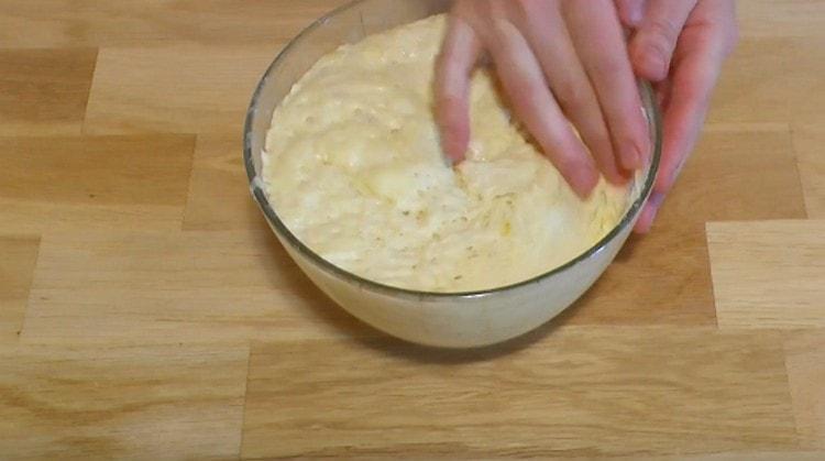 Смазанными маслом руками обминаем поднявшееся тесто.