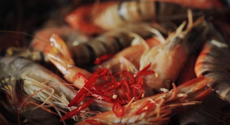 Выкладываем креветки, жарим, добавляем измельченный чеснок и перец чили.