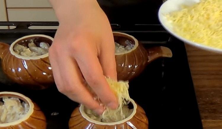 Перекладываем жульен в горшочки, посыпаем натертым на терке сыром.