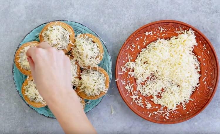 Посыпаем тарталетки с начинкой натертым сыром.