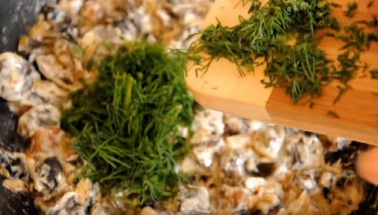 К грибам добавляем сметану, а также укроп.