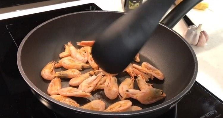 Выкладываем креветки на разогретую сухую сковороду.