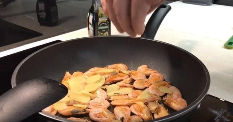 Добавляем имбирь на сковороду к креветкам.