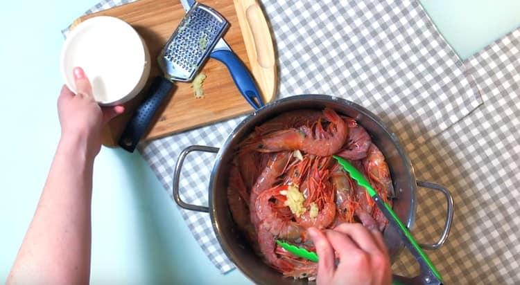Добавляем чеснок, имбирь, растительное масло и соль и перемешиваем морепродукты.