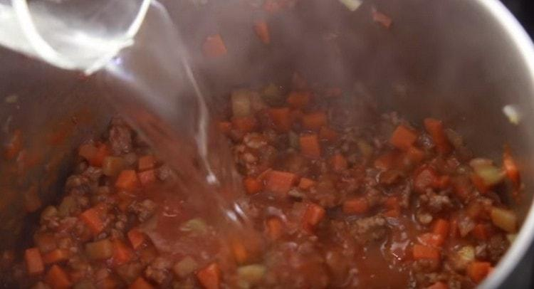 Добавляем томатную пасту и воду.