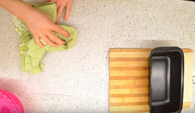 Смачиваем водой лист пергамента, вытираем его полотенцем и застилаем форму.